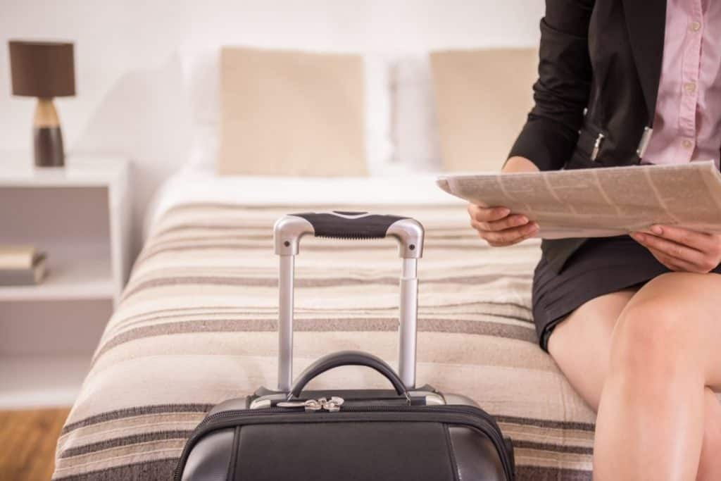 Woman with Samsonite luggage in hotel room
