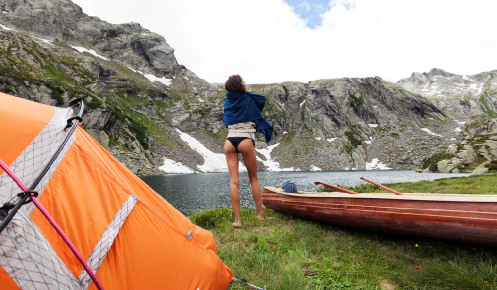 Beautiful girl in outdoor tent with canoe